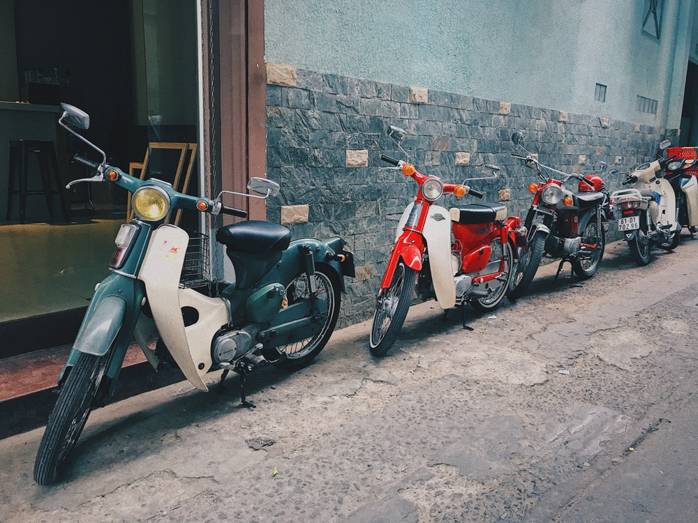 four parked assorted-color motorcycles