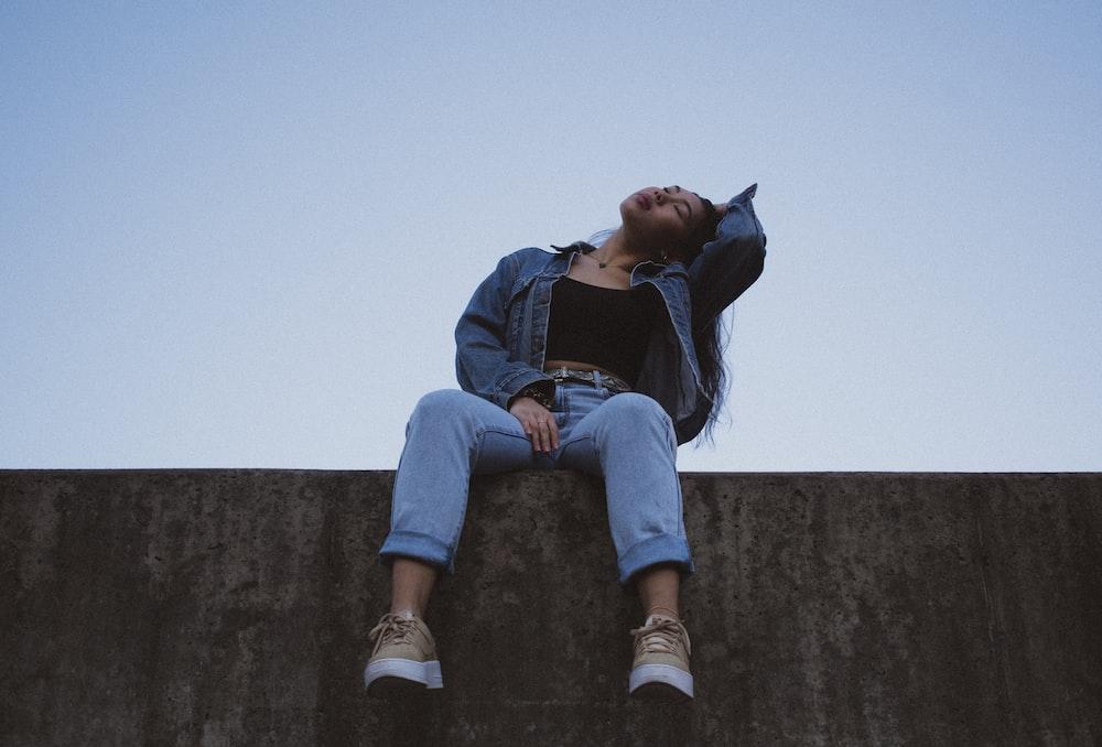 woman sitting on concrete