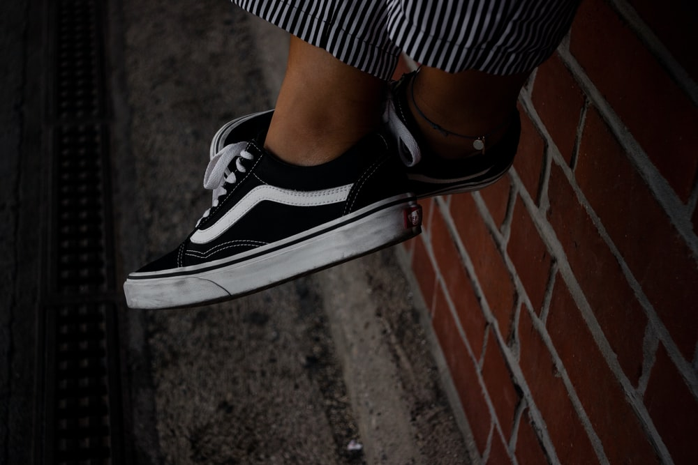 person wearing black-and-white Vans low-top sneakers