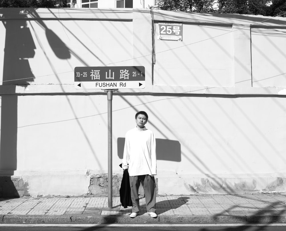 man standing near street post grayscale photo