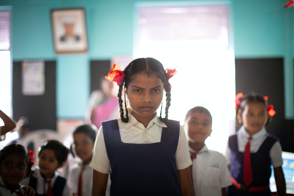 selective focus photography of standing girl in uniform inside blue painted room with classmates