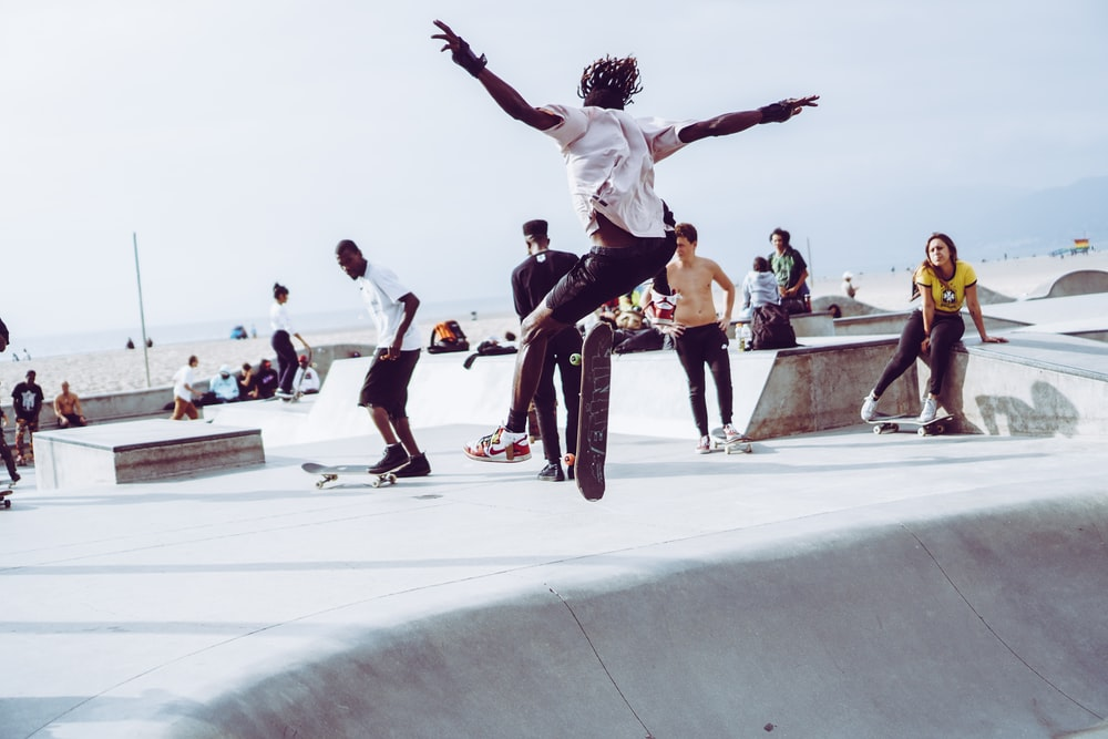 man in white t-shirt making skateboard stunts with other skateboarder
