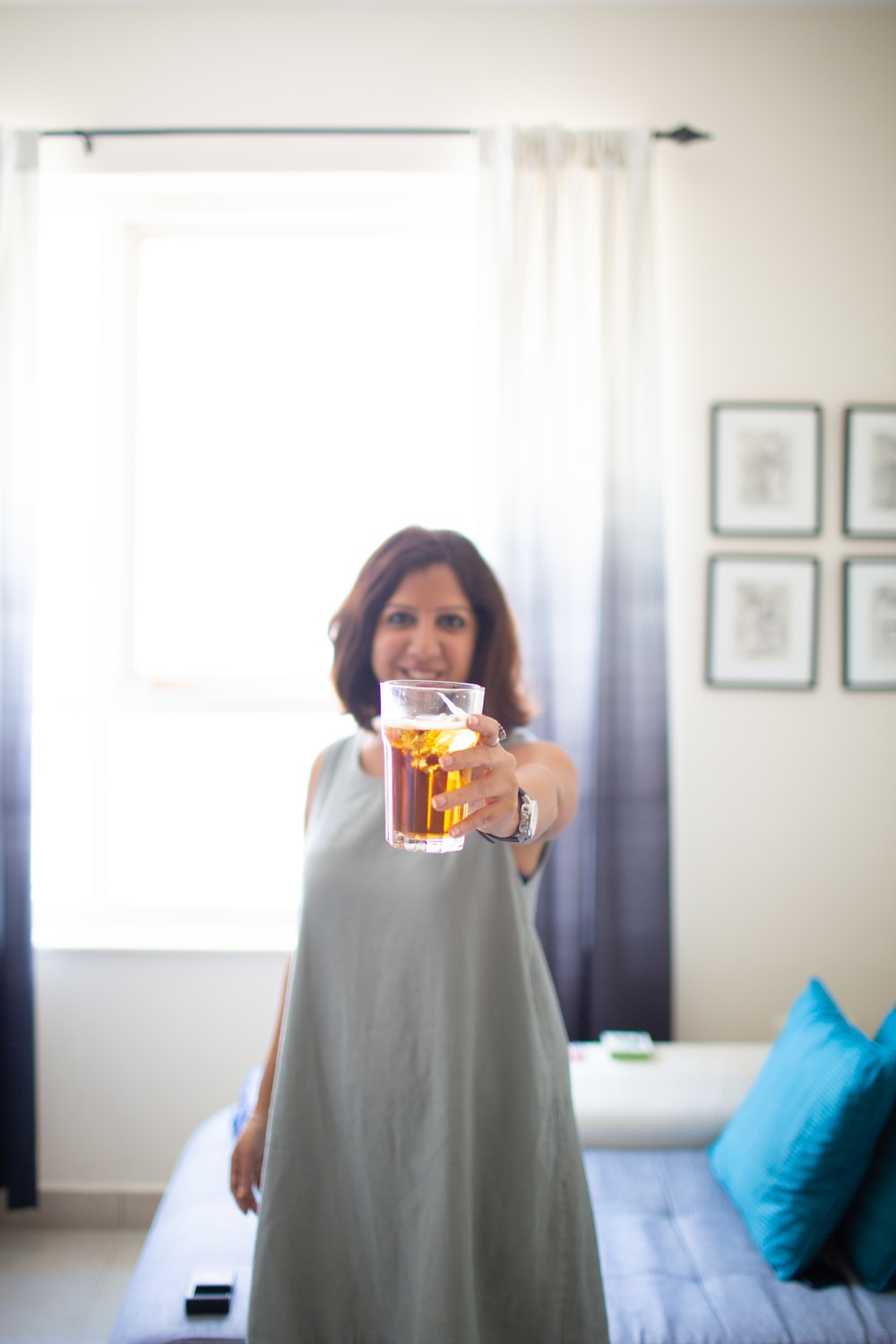 selective focus photography of standing woman holding out cup