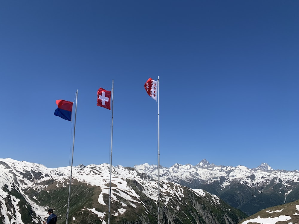 low-angle photography of three flags