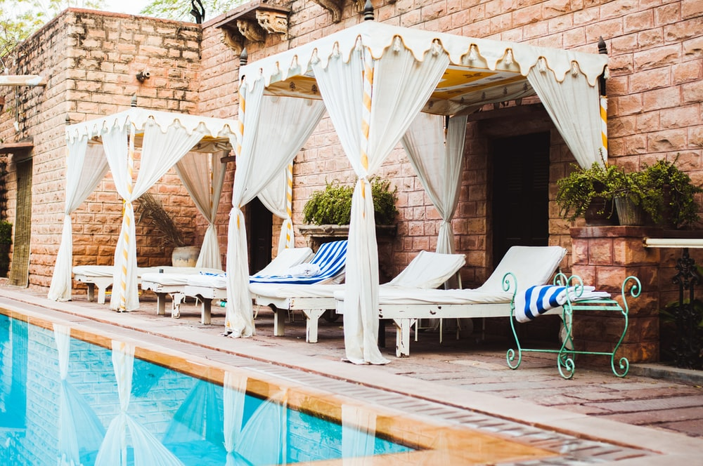 empty white loungers beside swimming pool