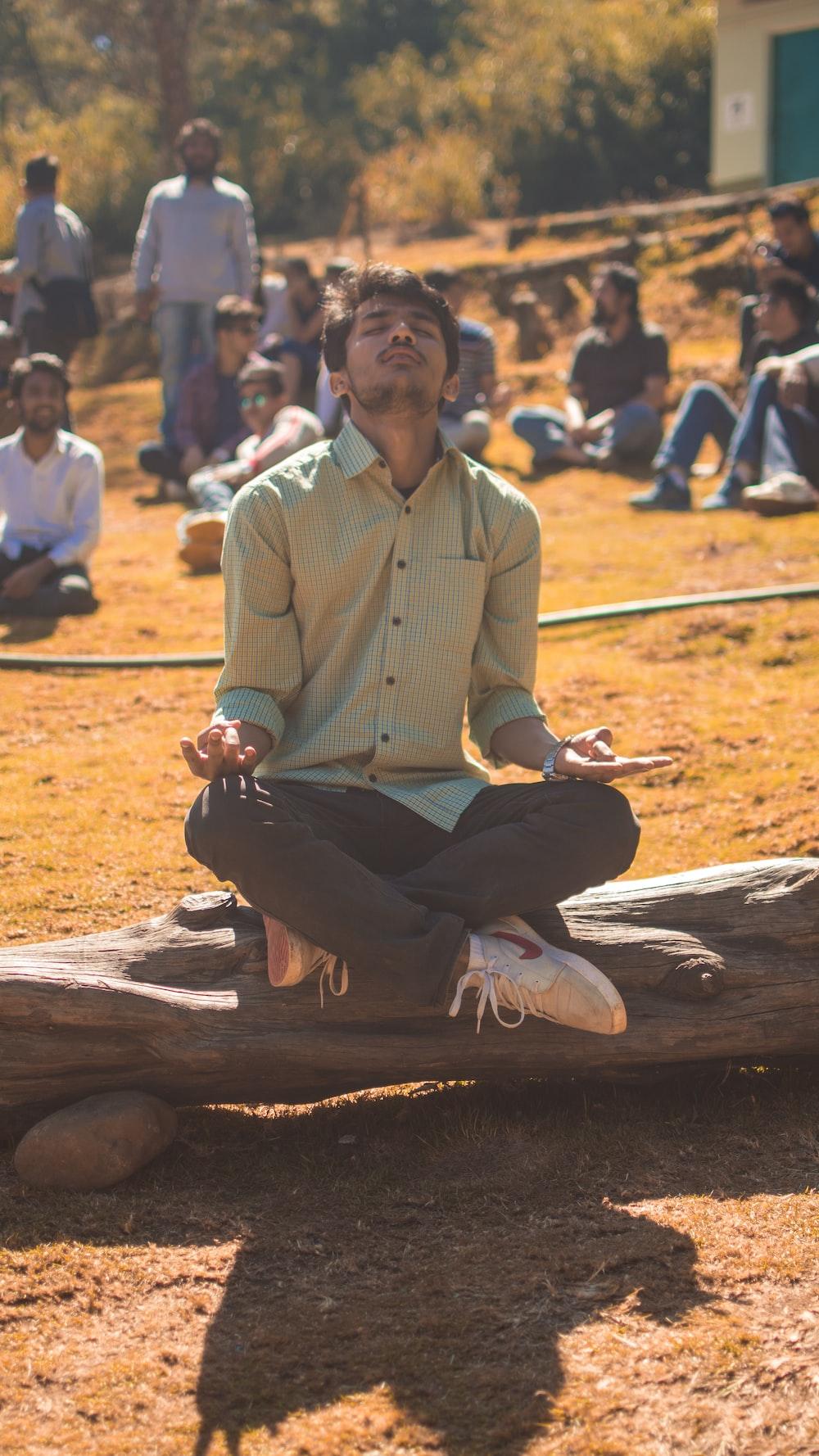man meditating on tree log