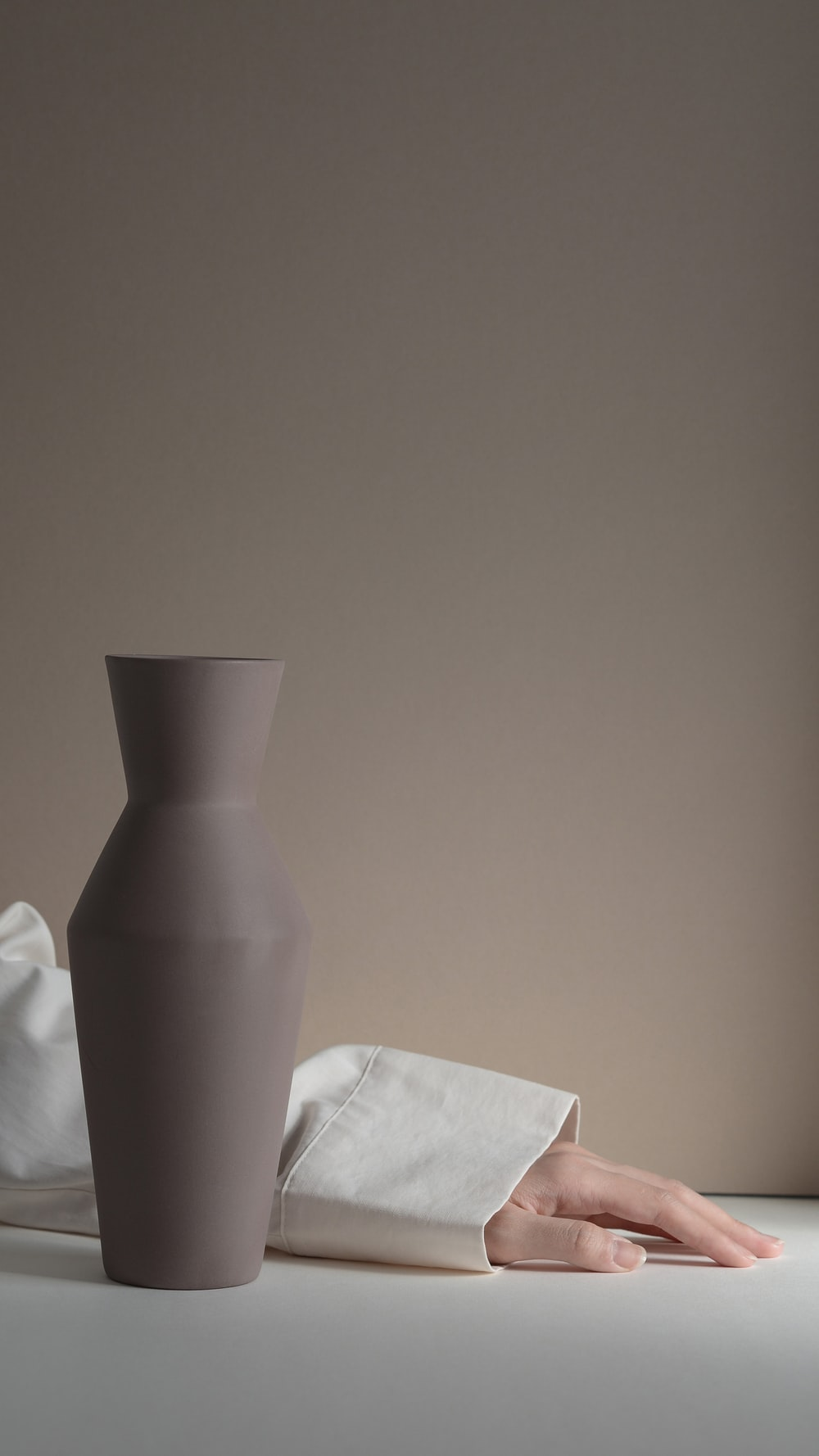 person's hand beside gray vase