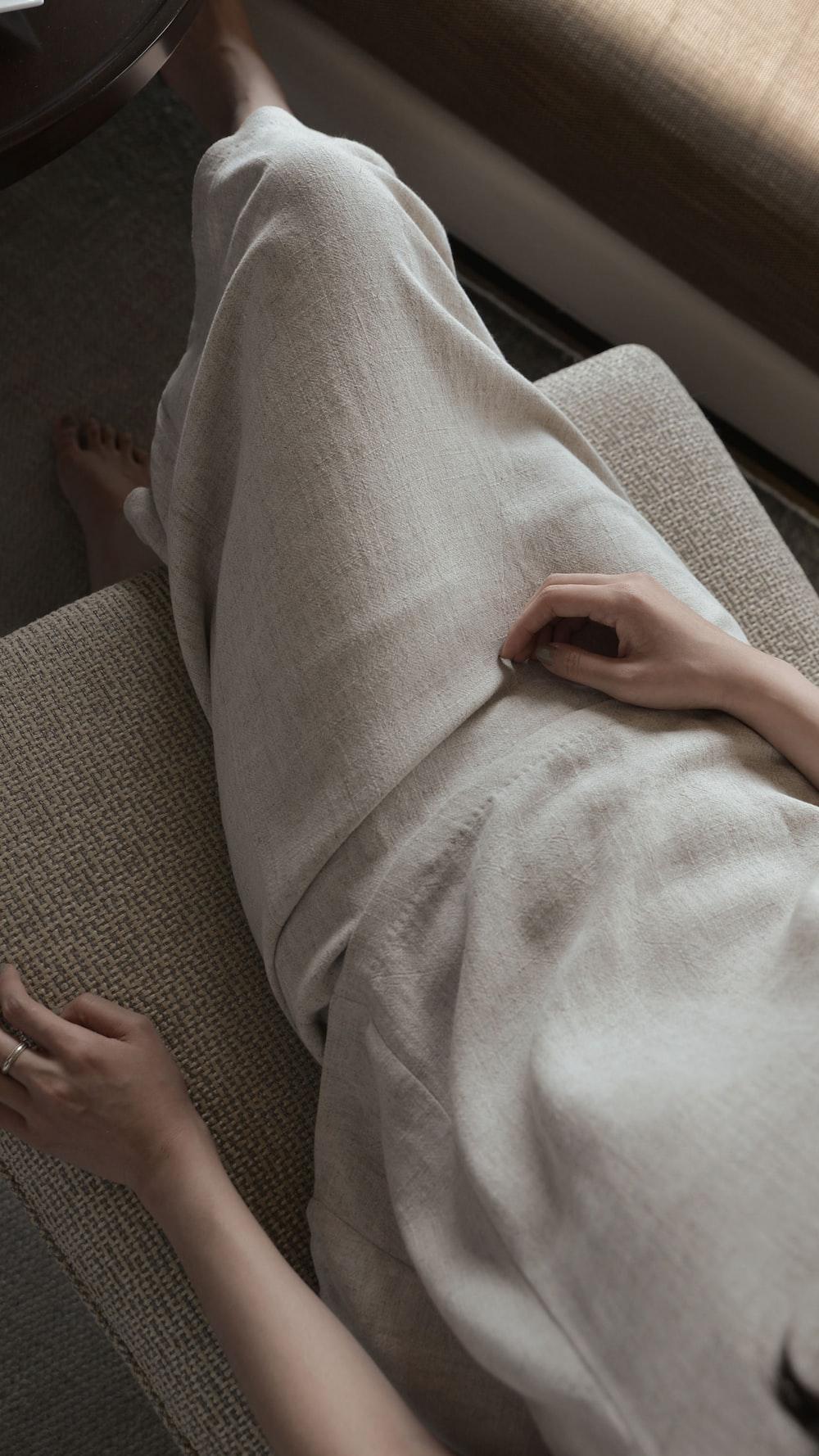 woman wearing white dress sitting sofa chair