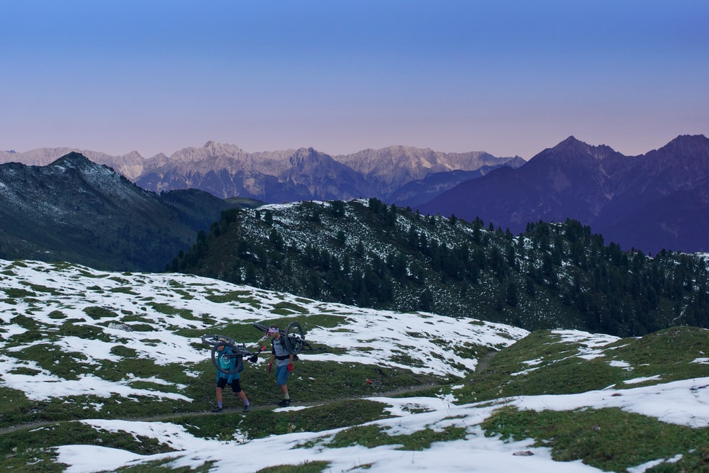 two men carrying bicycle walking on mountain