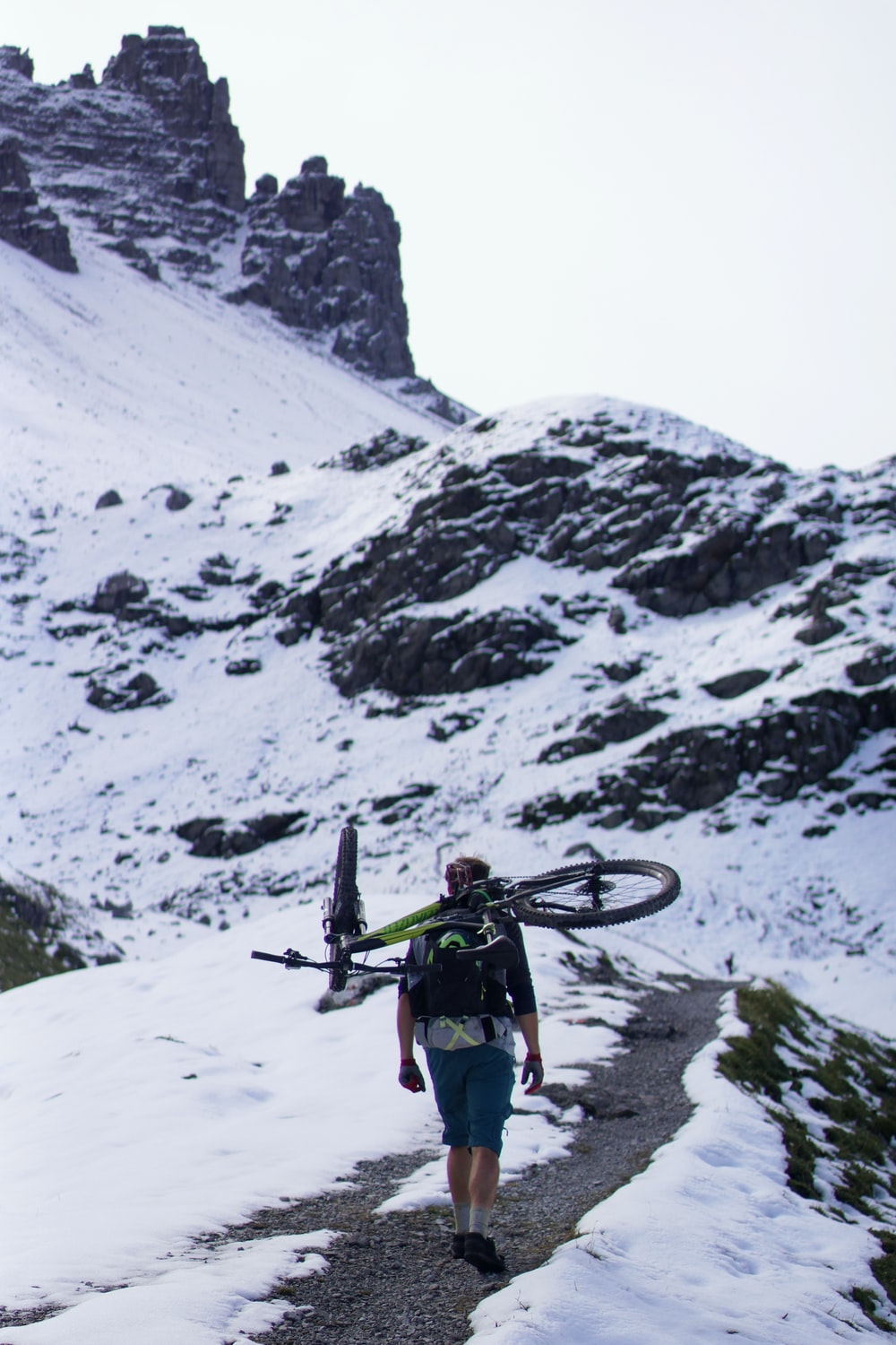 man carrying bicycle walking on mountain surrounded by snow