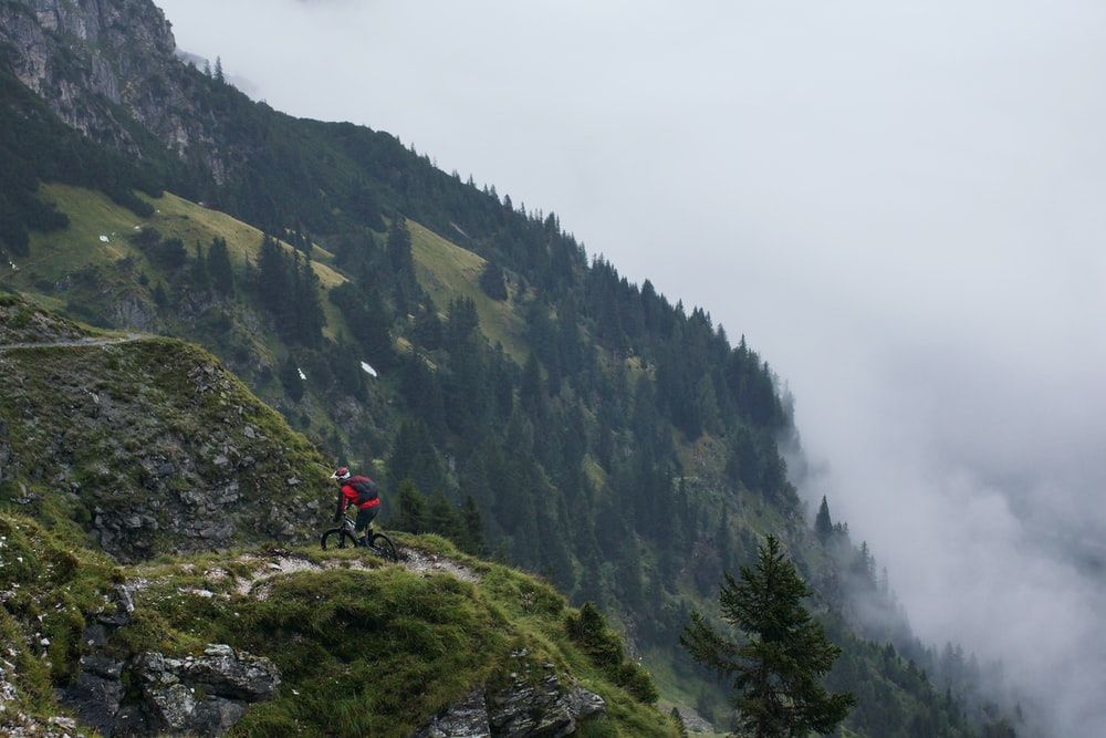 man riding on bicycle on top of mountain