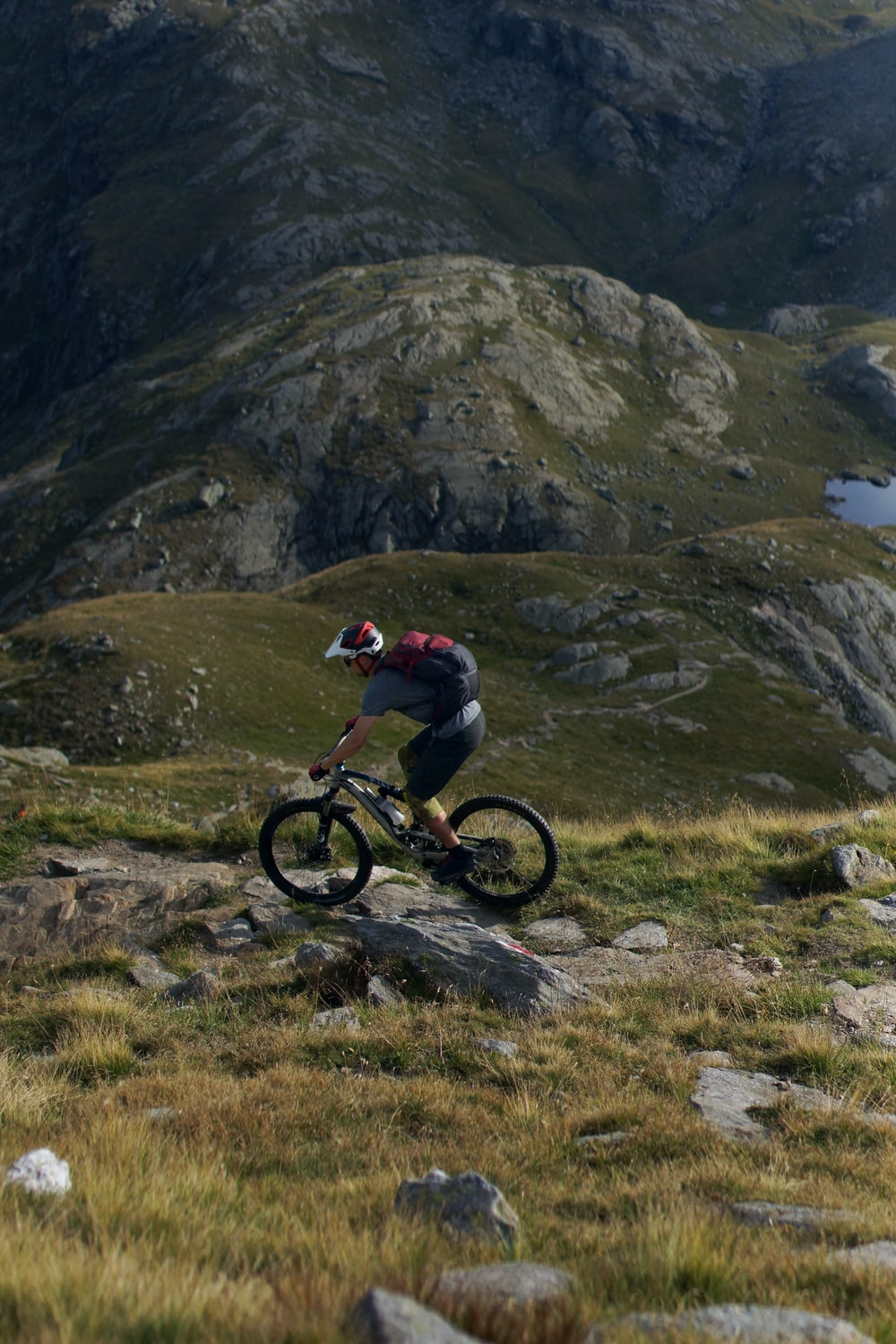 person cycling on green mountain