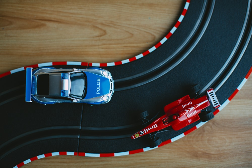 blue toy car beside red formula one toy