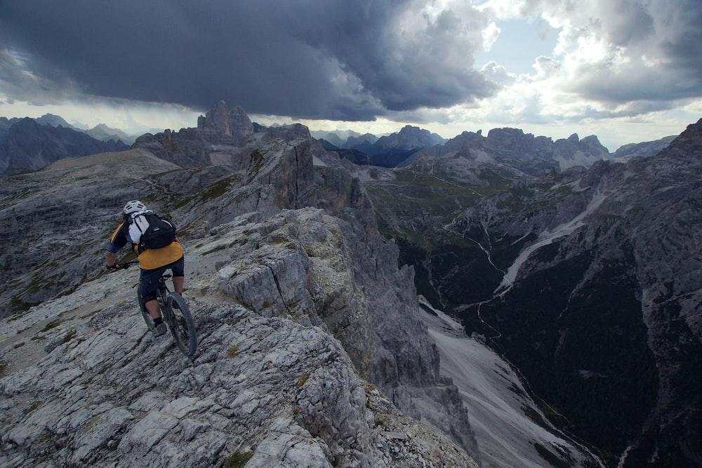 person wearing yellow shirt and black short riding on mountain bike
