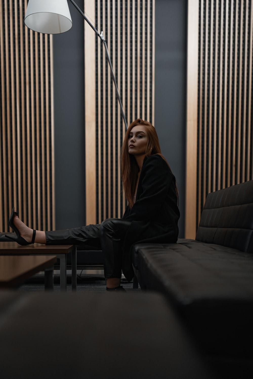 woman wearing black suit sitting on black leather sofa