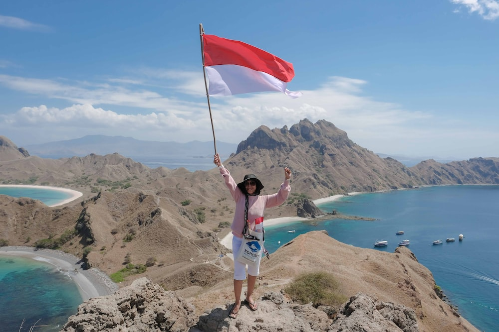 woman waving red and white flag on hill