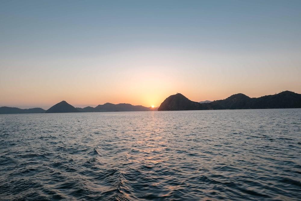 ocean near mountain during sunrise