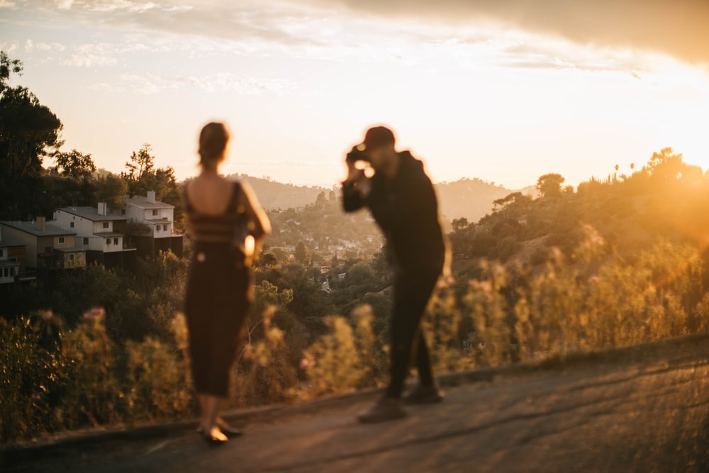 woman standing beside man holding DSLR camera