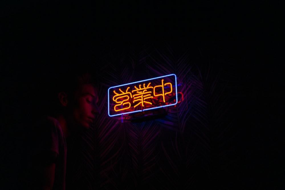 man near orange kanji LED lights
