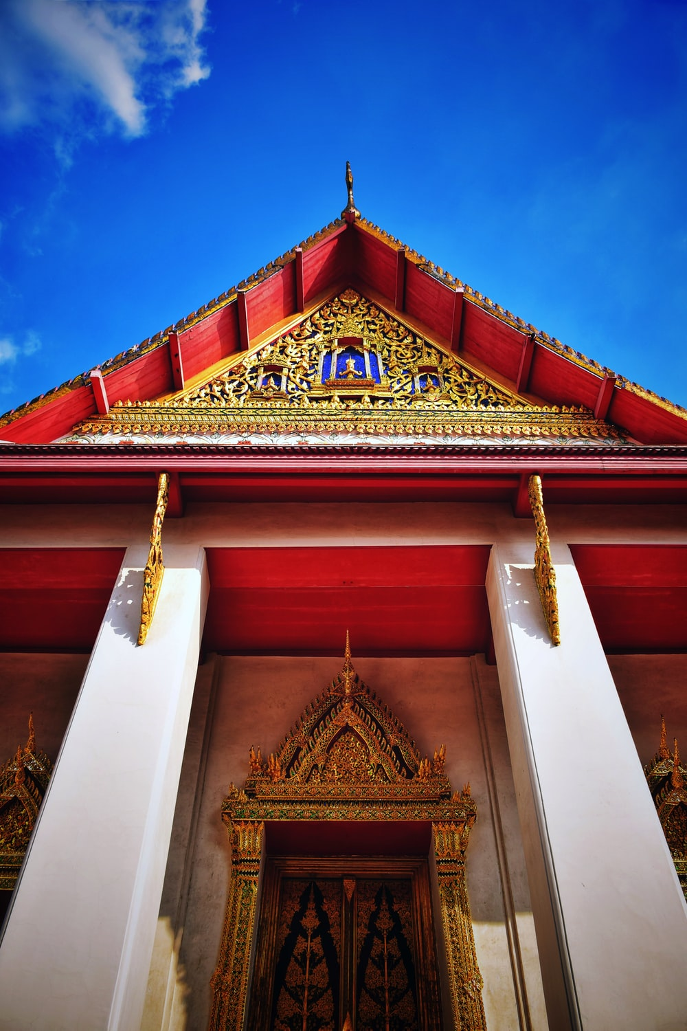 low-angle photography of red and gold temple under blue and white sky during daytime