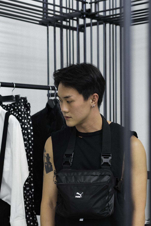 man in black puma bag near clothes display