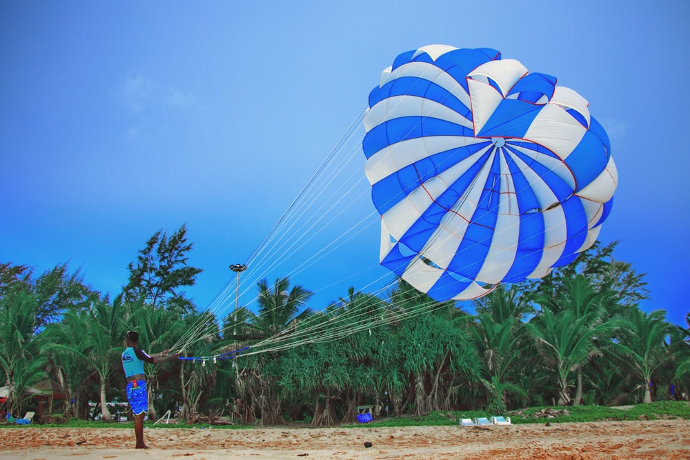 man standing while holding blue and white parachute under blue and white sky during daytime