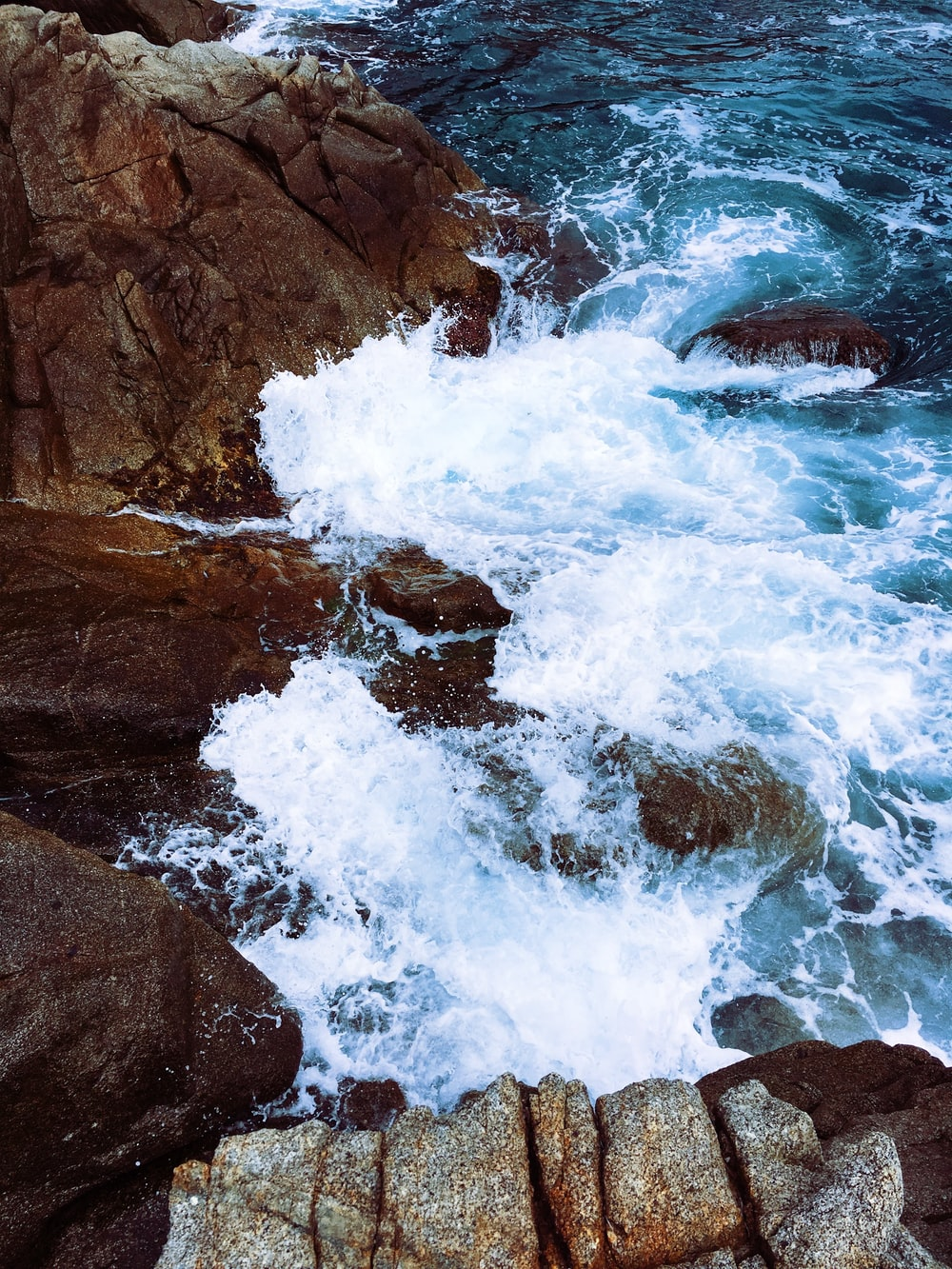 time lapse photography of waves splashing on rocks