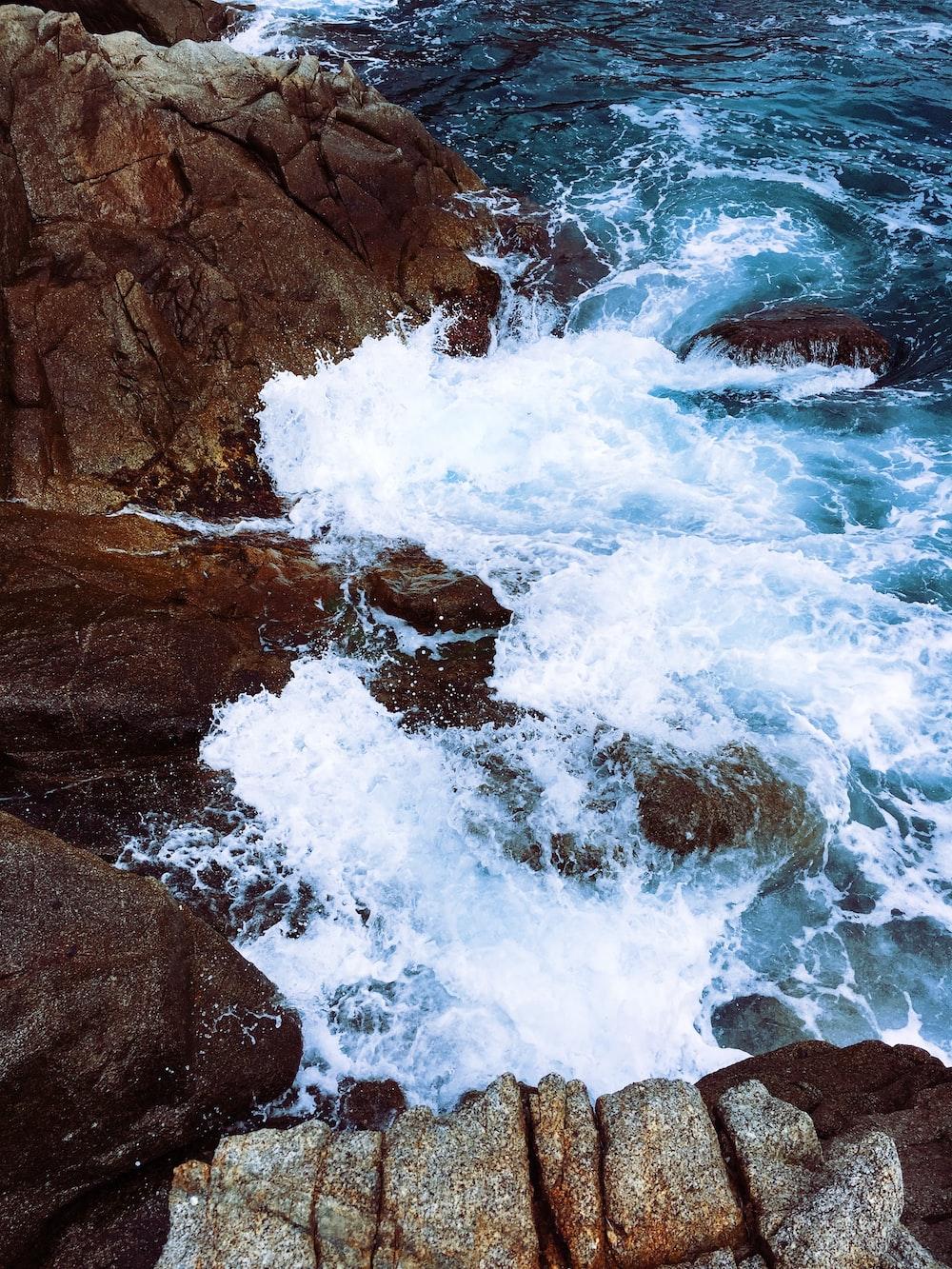 time lapse photography of waves splashing on rocks