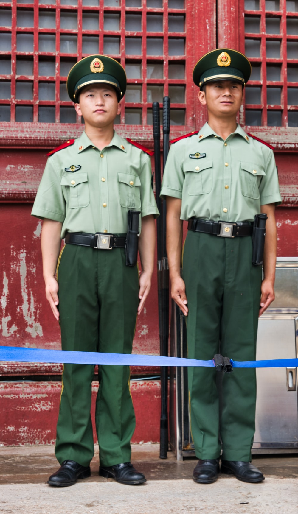 two boys wearing green collared button-up shirt with pockets standing