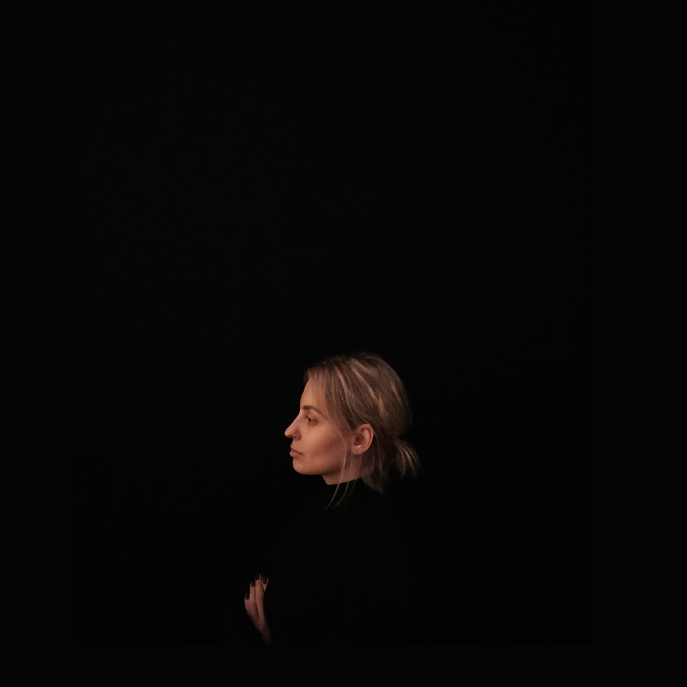 minimalist photography of woman wearing black top facing to the side