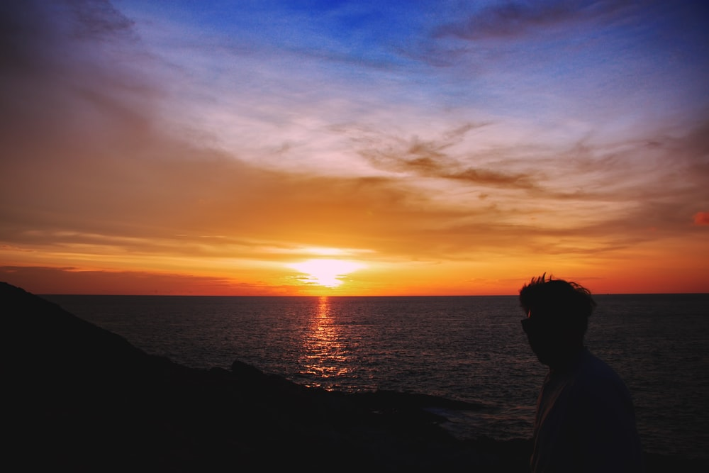 silhouette photography of man on shore