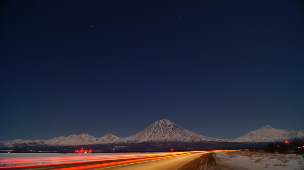 time lapse photography of car passing by a street leading to a snowy mountain