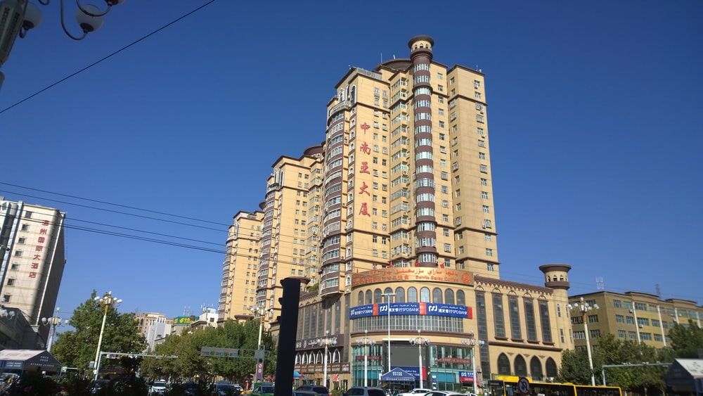 low-angle photography of beige concrete building under blue sky