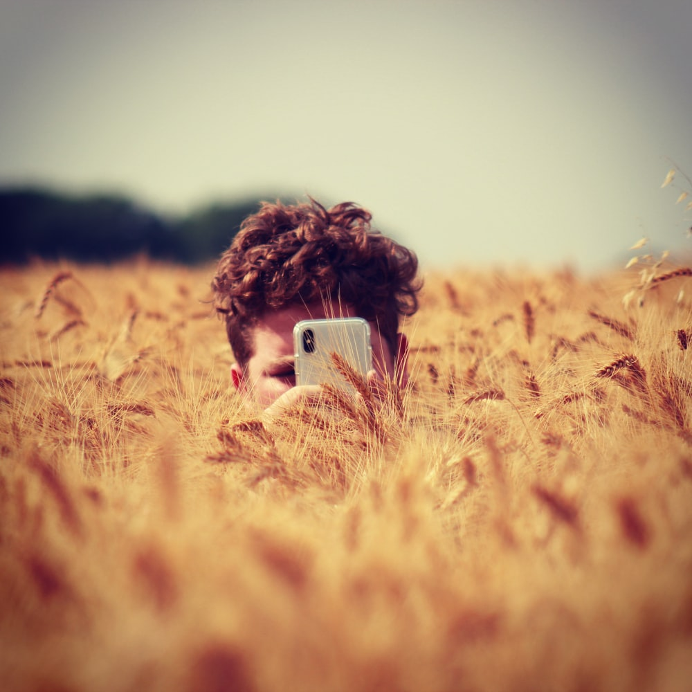 man holding silver iPhone X surrounded by grass