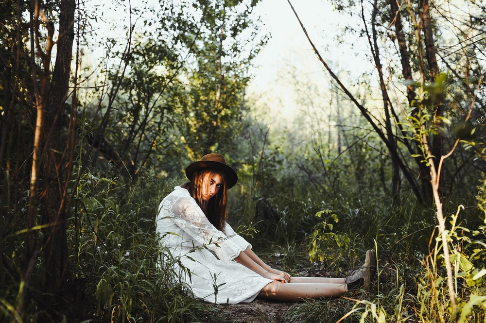 woman in white dress sitting surrounded by trees and grass during daytime