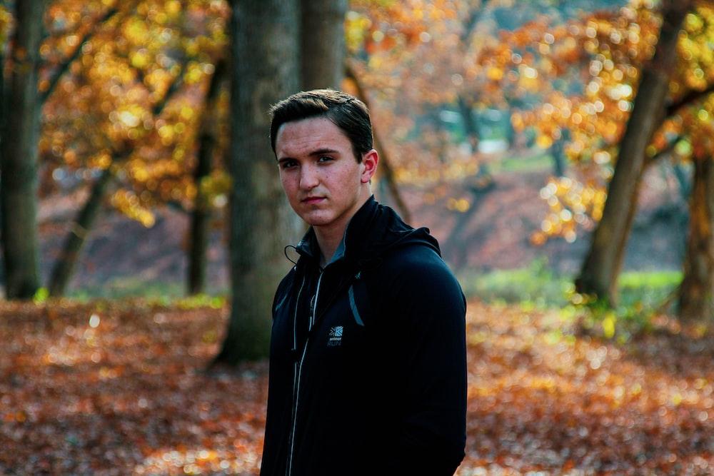 man wearing black zip-up hoodie surrounded by trees