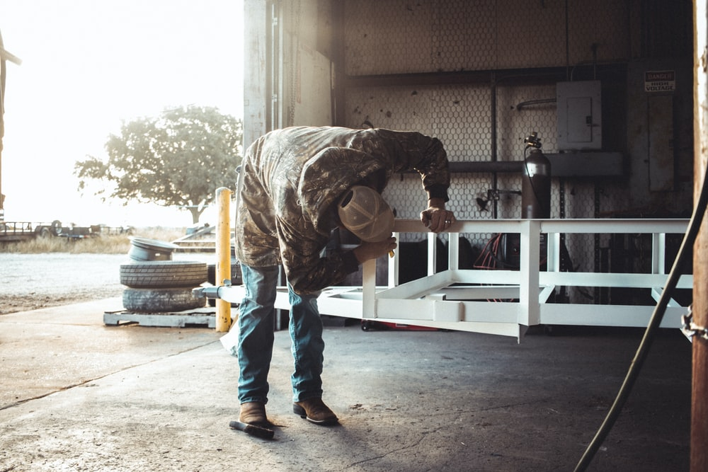 man leaning down on a metal frame