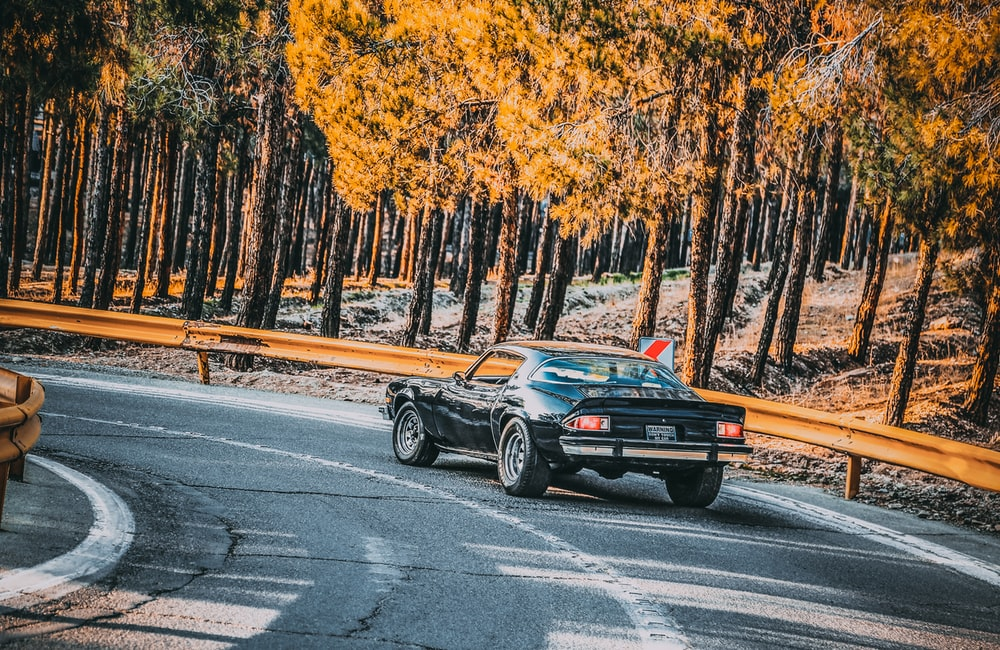 black coupe traveling on road