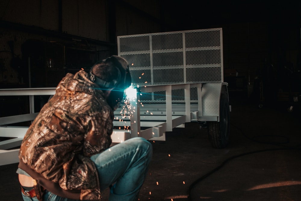 man welding white utility trailer