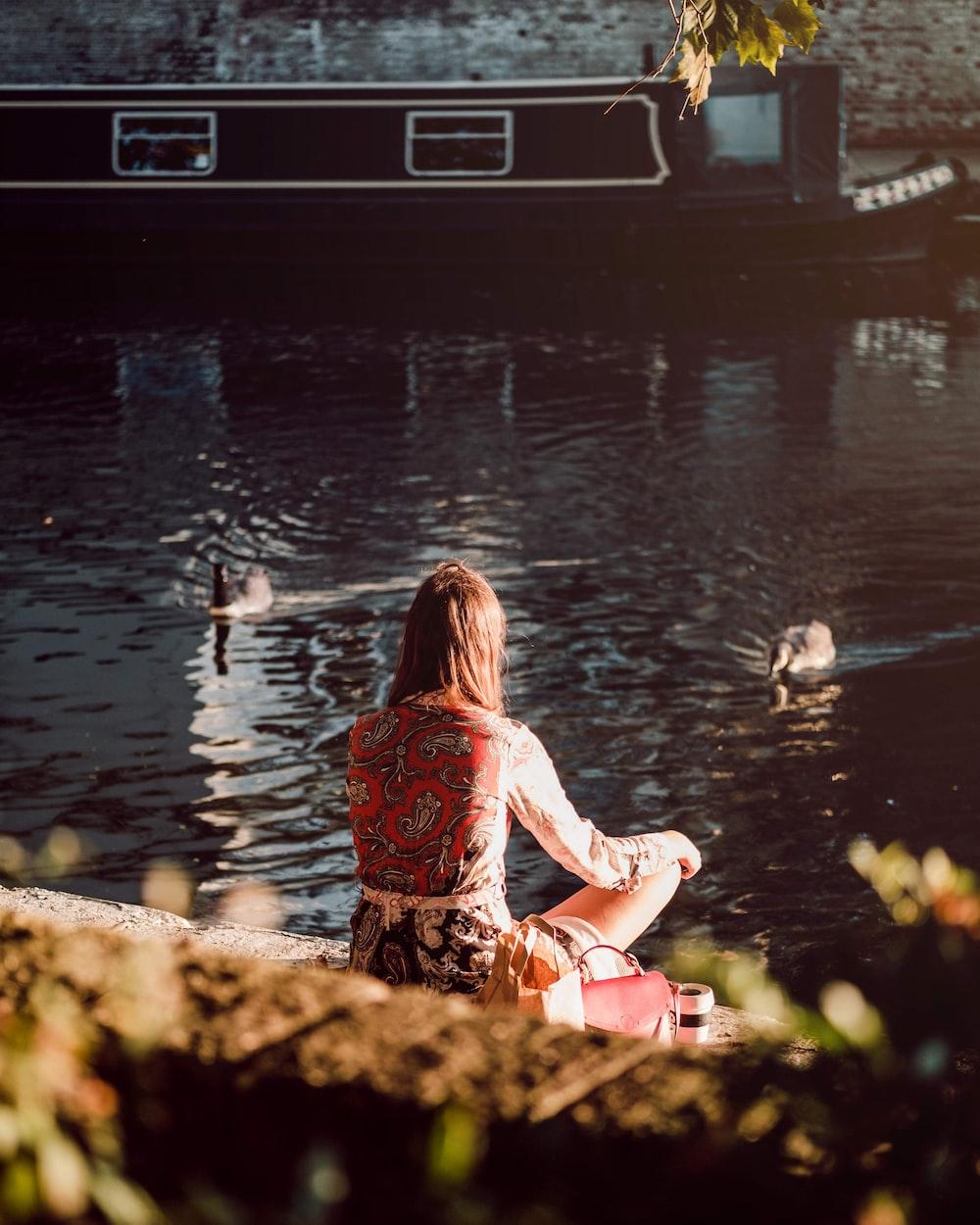 woman sitting near pond