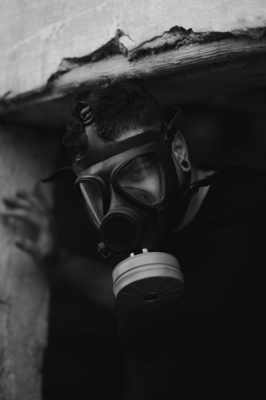 man wearing gas mask inside door