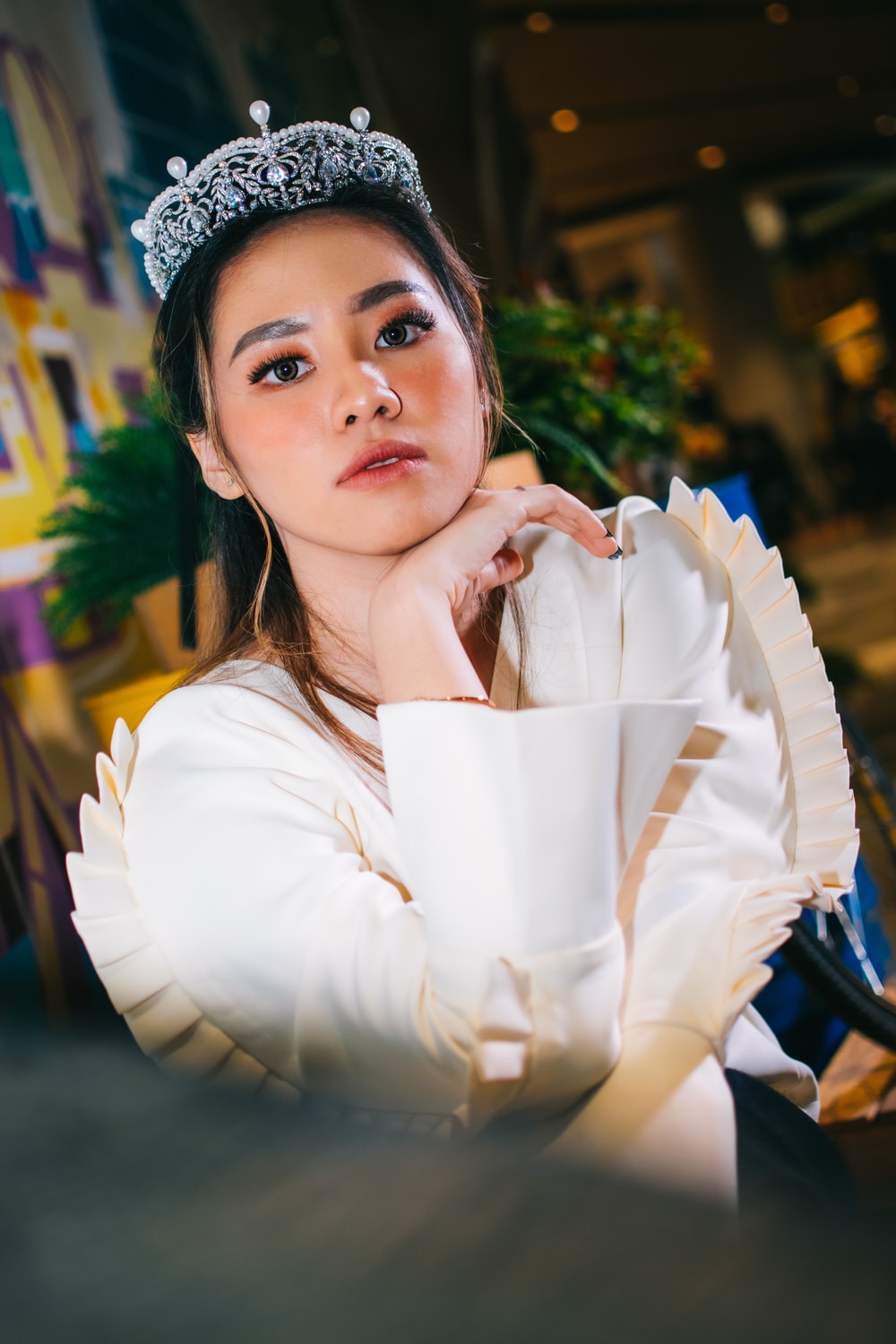 woman wearing white long-sleeved top and silver crown