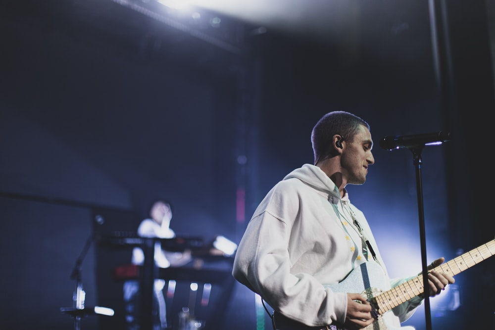 man playing an electric guitar on stage