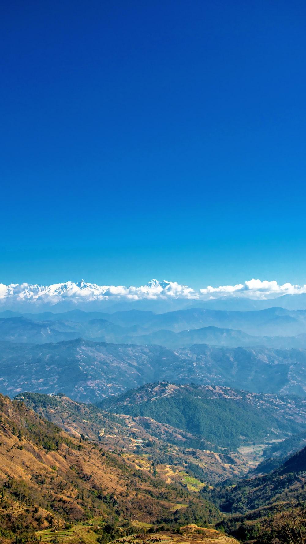 mountain ranges under blue clouds