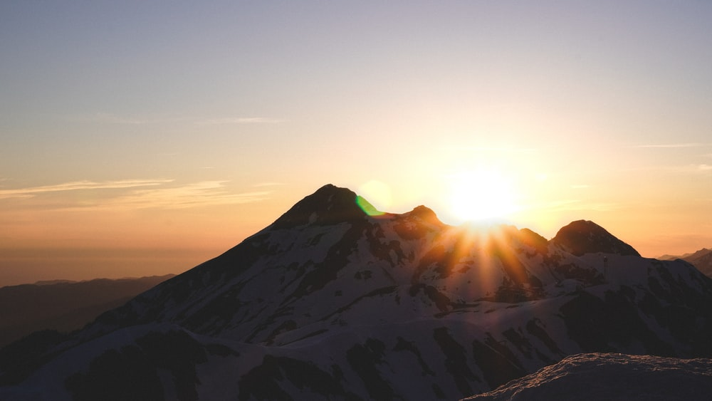 sun rays coming through mountain under orange sky