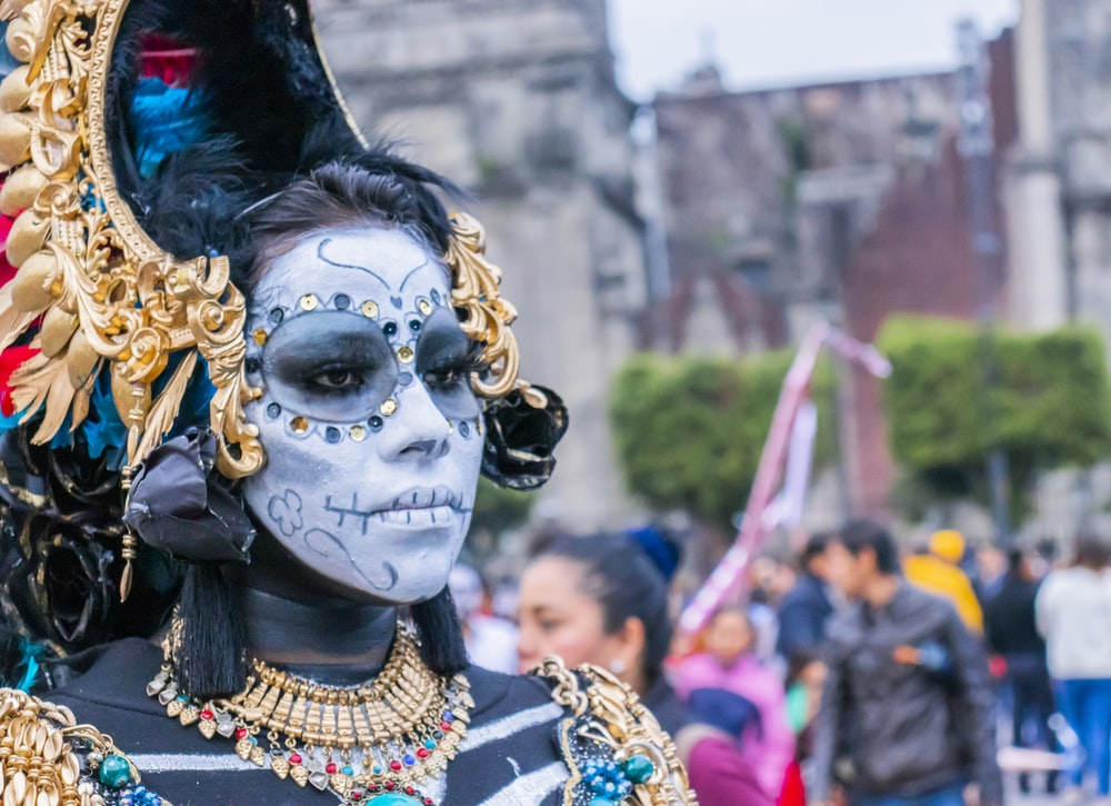 woman wearing gold-colored accessories and face paint