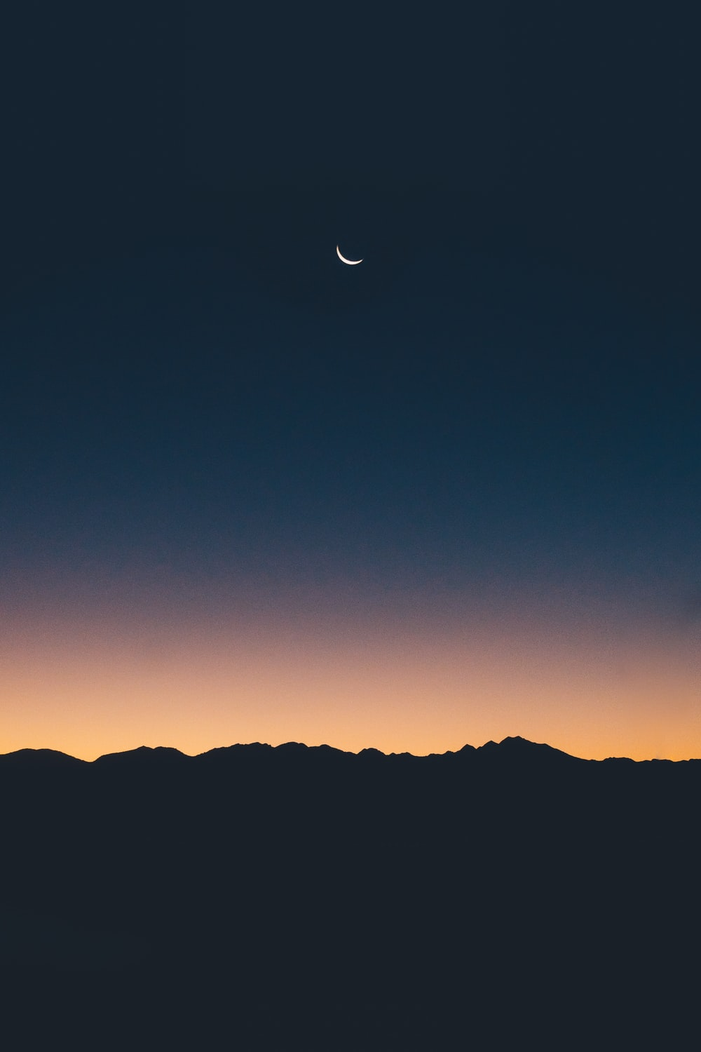 silhouette photography of land under a crescent moon during golden hour