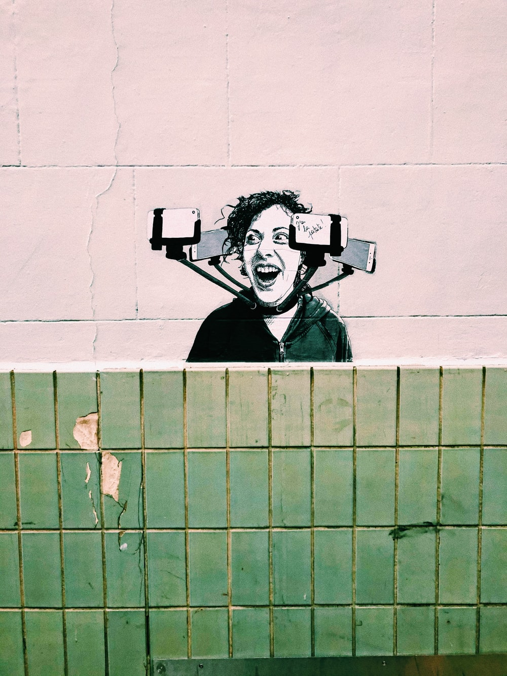 mural painting of woman's face surrounded by smartphones