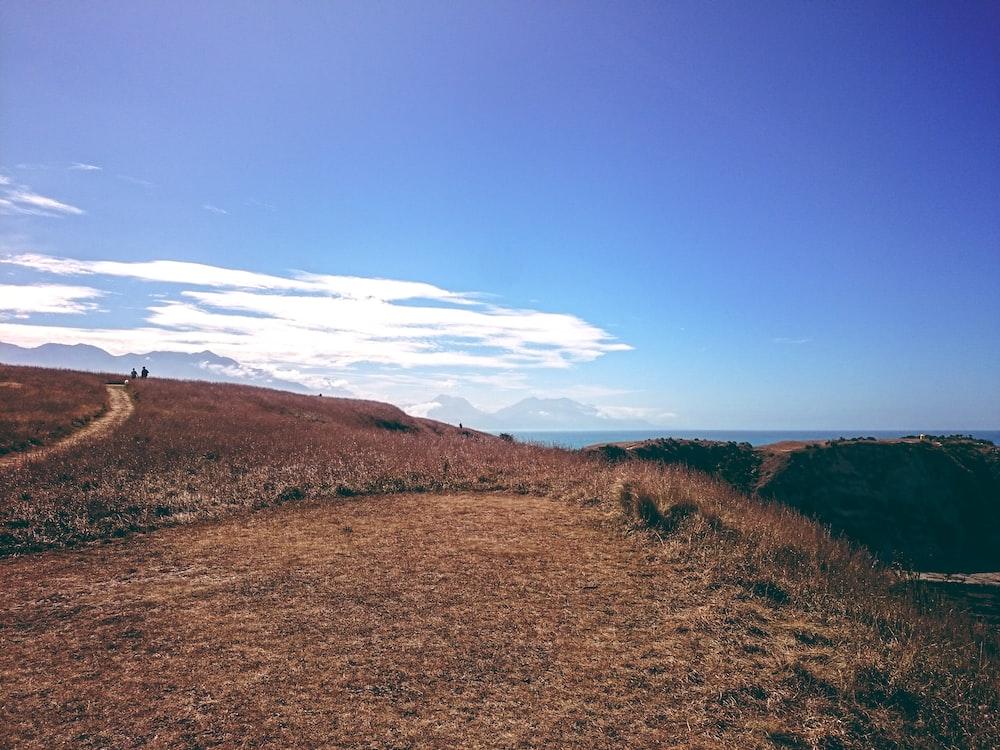 hill under blue cloudy sky