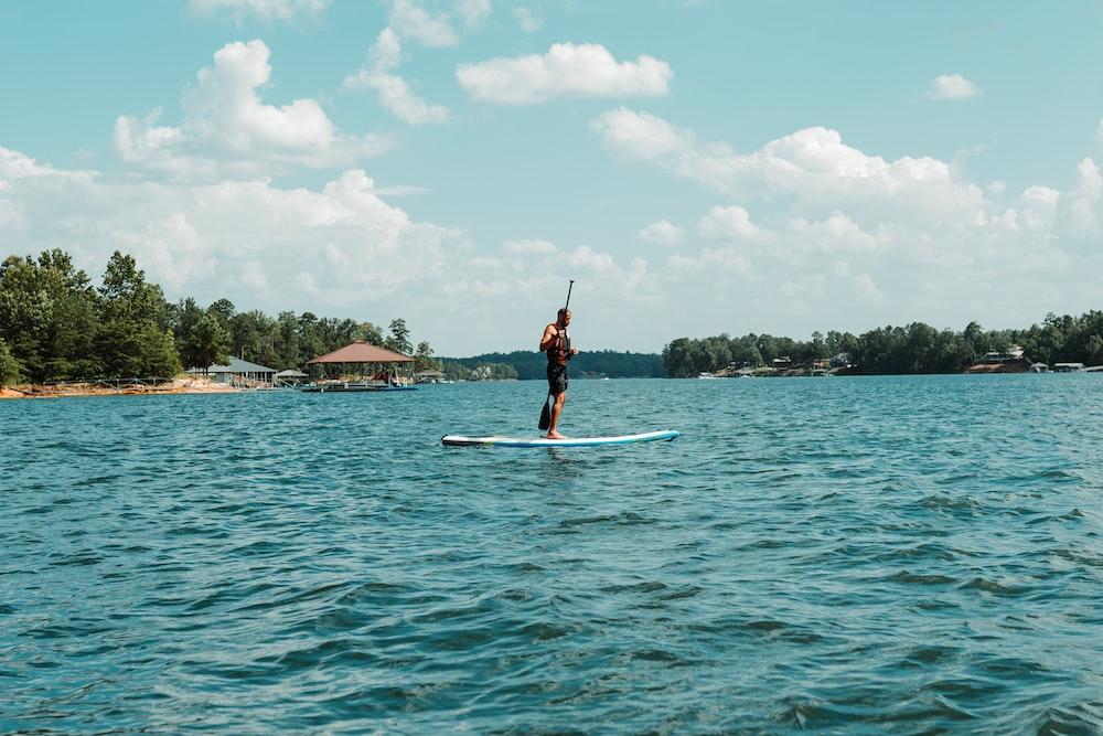 man standing on surfboard